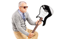 Angry mature man breaking an electric guitar. Isolated on white background Stock Photos