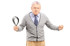 Angry mature man holding a belt and posing. Isolated on white background stock images
