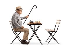 Angry mature man playing chess royalty free stock photo