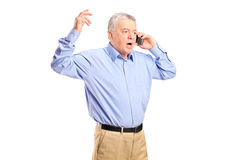 Angry mature man talking on the phone. Isolated on white background stock photos