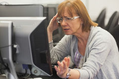 Angry mature student working with computer Stock Photography