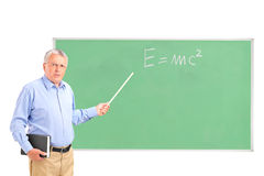 An angry mature teacher and chalkboard. An angry mature teacher with a book in his hand and chalkboard in the background Royalty Free Stock Image