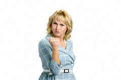 Angry mature woman making a fist. Frowning white-skin woman putting up fist over white background Stock Image