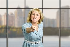 Angry mature woman pointing forward. Stock Images
