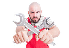 Angry mechanic or plumber holding crossed wrenches stock image