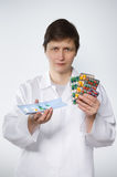 Angry medic with many pills in hands on gray background. Angry medic with many pills in hands on neutral background royalty free stock images