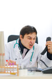 Angry medical doctor shouting in phone handset. Angry young medical doctor shouting in phone handset Royalty Free Stock Image