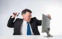 Angry men holding hammer over PC monitor Stock Photo