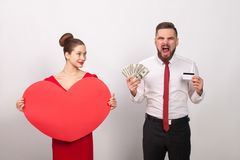 Angry man roar, his pays for love, woman smiling. Angry men roar, his pays for love, women smiling. Indoor, studio shot, on gray background royalty free stock photos