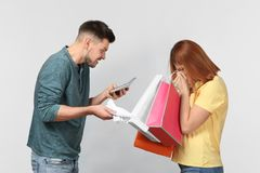 Angry man scolding his wife who has spent   of money for shopping, against light background. Angry men scolding his wife who has spent a lot of money for Royalty Free Stock Images