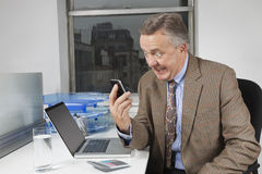 Angry middle-aged businessman looking at cell phone in office Royalty Free Stock Image