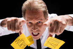 Angry middle aged businessman with sticky notes on clothes pointing at camera Stock Photo