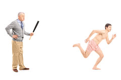 Angry middle aged man with baseball bat shouting at a naked man Stock Photos