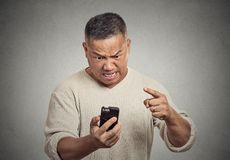 Angry middle aged man while on mobile, pointing at smart phone. Closeup portrait angry middle aged man, guy, mad worker, pissed off employee while on mobile Stock Photography