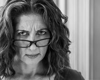 Angry Middle Aged Woman. Angry middle aged female teacher frowning over her glasses Royalty Free Stock Image