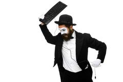 Angry mime as a businessman is destroying. A keyboard. isolated on white background Stock Images
