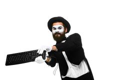 Angry mime as a businessman is destroying. A keyboard. isolated on white background Stock Photo