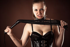 Angry mistress with a whip. In hands royalty free stock image