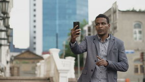 Angry Mixed race businessman having online video chat in business conference using smartphone stock footage