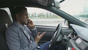 Angry mixed race businessman talking phone while sitting inside his car outdoors. Angry african american businessman talking phone while sitting inside his car stock video footage