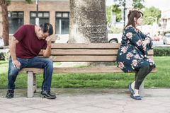 Angry Mixed Race Couple Sitting Facing Away From Each Other on Park Bench royalty free stock photo