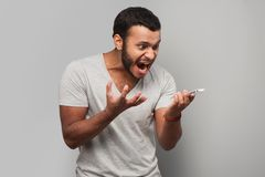 Angry mixed race man screaming at phone. Young mixed race man screaming at phone, standing on grey background Stock Photos