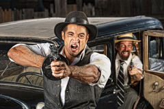 Angry Mobsters Shooting Gun. Angry mobsters firing submachine gun near antique car stock image