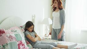 Angry mother argue scolding her upset little daughter lying on bed in bright bedroom at home. Angry mother argue scolding her upset little daughter lying on bed stock footage