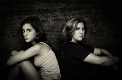 Angry mother and her teenage daughter sitting back to back royalty free stock photos