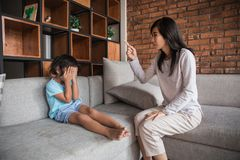 Angry mother scolding daughter. Covering her face in living room royalty free stock photos
