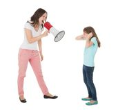 Angry mother shouting through megaphone at daughter. Full length of angry mother shouting through megaphone at daughter against white background Royalty Free Stock Images