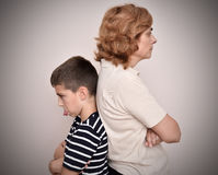 Angry mother and son. Sticking his tongue out with their backs to each other Stock Photo