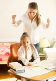 Angry mother swears on daughter doing homework Royalty Free Stock Images