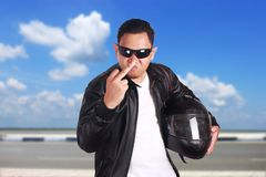 Angry Motorcyclist Biker Racer Shows Middle Finger. Portrait of young attractive Asian man wearing black leather jacket and sunglasses showing middle finger Royalty Free Stock Photos