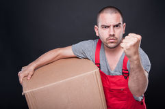 Angry mover man holding box showing fist. Gesture like fighting on black background Stock Photos