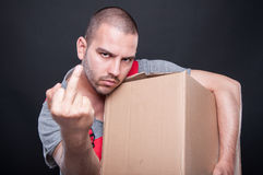 Angry mover man holding box showing obscene gesture. On black background Royalty Free Stock Photos