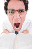 Angry nerd in shirt and tie with glasses holding open book Royalty Free Stock Images