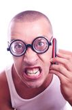 Angry nerd talking on a cell phone. Portrait of an angry nerd in eyeglasses talking on a cell phone Royalty Free Stock Photography