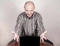 Angry and nervous businessman with a laptop Stock Photography