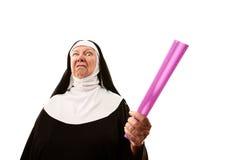 Angry Nun. Angry senior nun weilding purple ruler as weapon stock photo