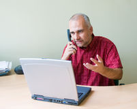 Angry office worker on the phone. Working at the desk with laptop stock image
