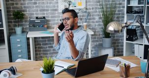 Angry office worker young Arab talking on mobile phone at desk feeling irritated. Angry office worker young Arab is talking on mobile phone at desk feeling stock video footage