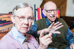 Angry Old Couple in Livingroom. Angry old couple sitting in living room women pointing Royalty Free Stock Photo