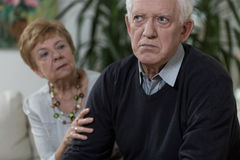 Angry old man. Lady is apologisong her sad and angry husband Royalty Free Stock Photography