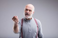 Aged angry man threatin with a punch. Angry old man menacing you with violence and a serious punch Royalty Free Stock Image