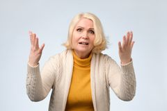 Angry old woman arguing with her husband. Wearing yellow sweater. She is dissatisfied with his decisions stock image