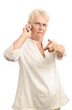 Angry old woman with cell phone Stock Photography