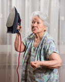 Angry old woman with an iron Royalty Free Stock Photography