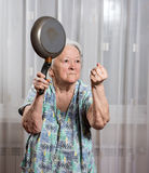 Angry old woman with a pan Royalty Free Stock Photography