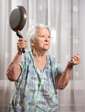 Angry old woman with a pan Stock Photo
